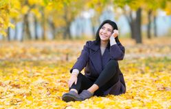 Happy young woman sitting daydreaming in a park. royalty free stock image