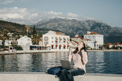 Happy Young woman sitting on Embankment with the laptop. Vacatio Stock Images
