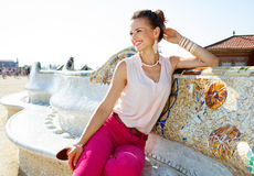 Happy young woman sitting on the famous trencadis style bench Stock Photos