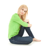 Happy young woman sitting on the floor Stock Photo