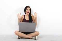 Happy young woman sitting on floor with crossed legs and using laptop on white background Stock Photo
