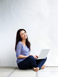Happy young woman sitting on floor at home with a laptop Royalty Free Stock Photo