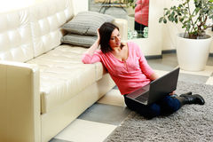 Happy young woman sitting on the floor with laptop Stock Photography