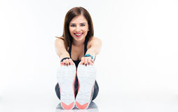 Happy young woman sitting on the floor and stretching Royalty Free Stock Photo