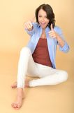 Happy Young Woman Sitting on Floor with Thumbs Up Stock Images