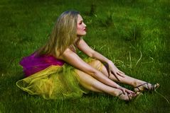 Happy young woman sitting on grass Royalty Free Stock Images