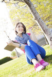 Happy young woman sitting on grass  listening to music and enjoyi Royalty Free Stock Photography