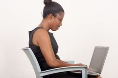 Young businesswoman working on a laptop on gray background stock photo
