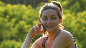 Happy young woman sitting on green lawn and talking on the phone or smartphone stock video footage