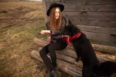 Happy young woman sitting with her black dog in fron of old wooden house stock photo