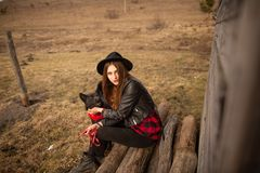 Happy young woman sitting with her black dog in fron of old wooden house.  royalty free stock images