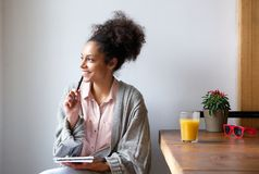 Happy young woman sitting at home with pen and paper Royalty Free Stock Image