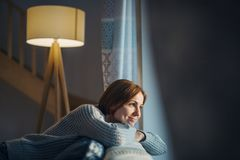 A young woman sitting indoors on a sofa at home, looking out of a window. A happy young woman sitting indoors on a sofa in the evening at home, looking out of a stock images