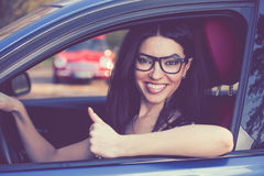 Happy young woman sitting inside her new car showing thumbs up Stock Image