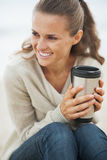 Happy young woman sitting on lonely beach with cup of beverage Royalty Free Stock Images