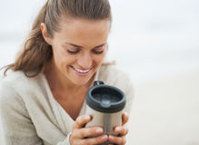 Happy young woman sitting on lonely beach with cup of beverage Stock Photo