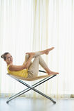 Happy young woman sitting on modern chair Royalty Free Stock Images