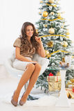 Happy young woman sitting near christmas tree Stock Photography