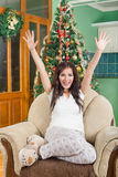 Happy young woman sitting near Christmas tree with raised hands Royalty Free Stock Images