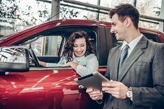 Happy young woman sitting in a new car at car salon professional salesman showing them information on digital tablet couple buying. Car info. Happy young women stock image