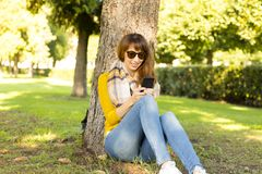Happy young woman sitting next to tree and typing message on the mobile phone Stock Image