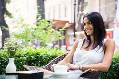 Happy young woman sitting in outdoors cafe Stock Photo