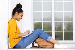 Happy young woman sitting outdoors writing a book Stock Image