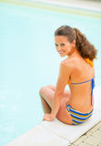 Happy young woman sitting at poolside Royalty Free Stock Image