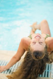 Happy young woman sitting at poolside Stock Photos