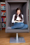 Happy young woman sitting and reading Stock Photos