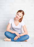 Happy young woman is sitting in room with blank wall Stock Photography