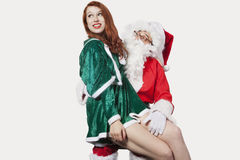 Happy young woman sitting on Santa's laps against gray background Stock Photography