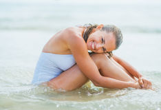 Happy young woman sitting on sea shore Stock Photos
