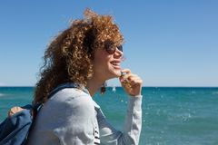Happy young woman sitting by seaside thinking. Portrait of happy young woman sitting by seaside thinking Stock Image