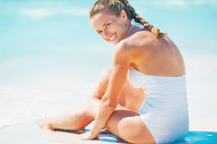 Happy young woman sitting at seaside Royalty Free Stock Image