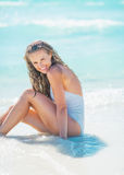 Happy young woman sitting at seaside Stock Photo