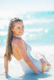 Happy young woman sitting at seaside Royalty Free Stock Photos