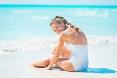 Happy young woman sitting at seaside Stock Photography