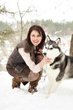 Happy young woman sitting with siberian husky dog Royalty Free Stock Image