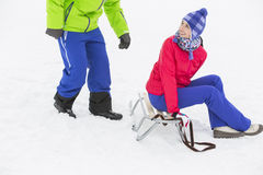 Happy young woman sitting on sled while looking at man in snow Royalty Free Stock Photography