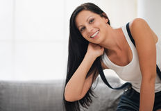 Happy young woman sitting on sofa Stock Photo