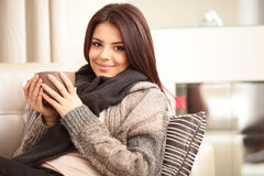 Happy young woman sitting on sofa. In cosy cloths with cup of coffee Royalty Free Stock Photography