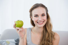 Happy young woman sitting on sofa holding green apple Stock Images