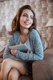 Happy young woman is sitting on sofa and holding tablet Royalty Free Stock Photography