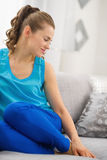 Happy young woman sitting on sofa in living room Royalty Free Stock Photography