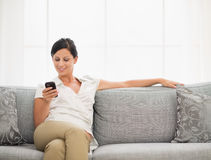 Happy young woman sitting on sofa and reading sms Stock Photo