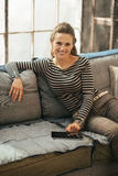 Happy young woman sitting on sofa and using tablet Royalty Free Stock Images