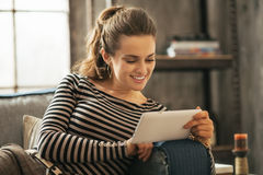 Happy young woman sitting on sofa and using tablet Stock Images
