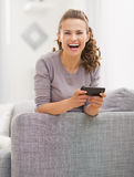 Happy young woman sitting on sofa and writing sms Royalty Free Stock Photo