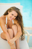 Happy young woman sitting on sunbed Stock Photo